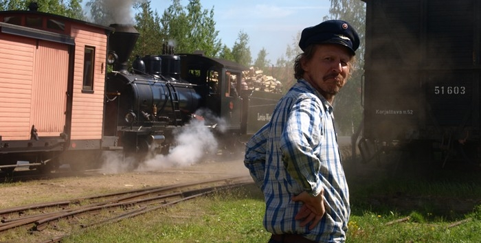 The switchman is smiling with a steam train on background.