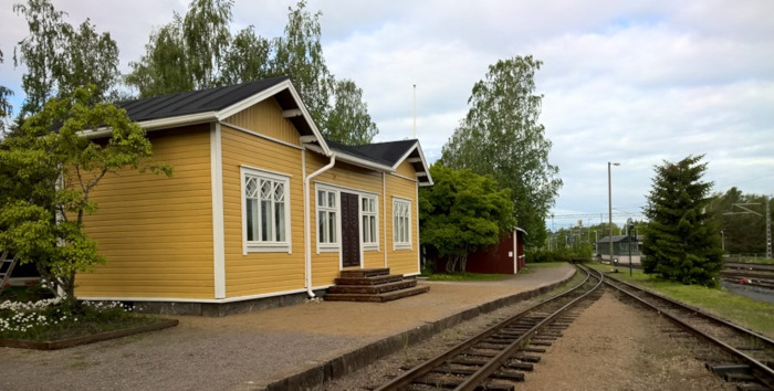 A yellow wooden railway station building.
