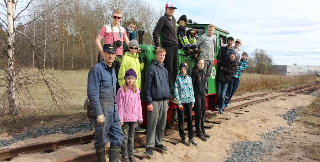 Young people standing in front of a green diesel locomotive.