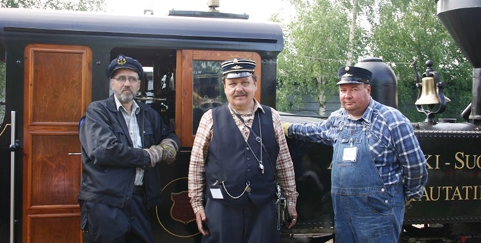 Staff in uniforms in front of a steam locomotive.