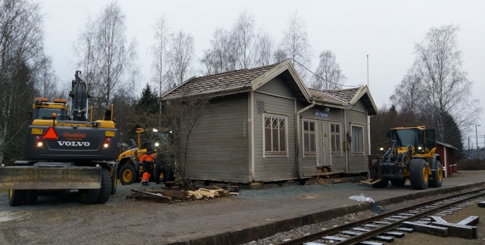 Wooden station building surrounded by orange tarctors.